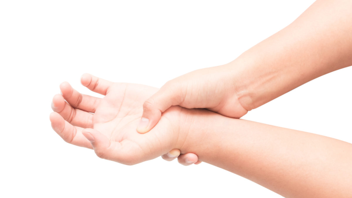 Woman hand holding her wrist on white background, health care and medical concept